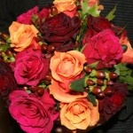 Hot pink, bright orange and deep red rose and Hypericum bouquet